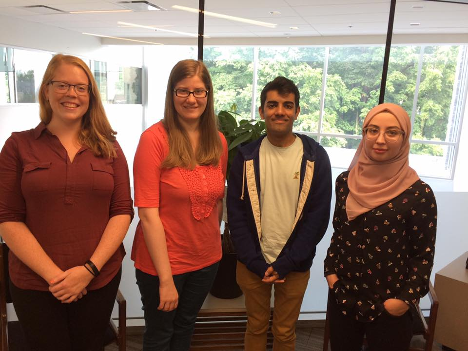 Four library student assistants standing in row in front of glass window