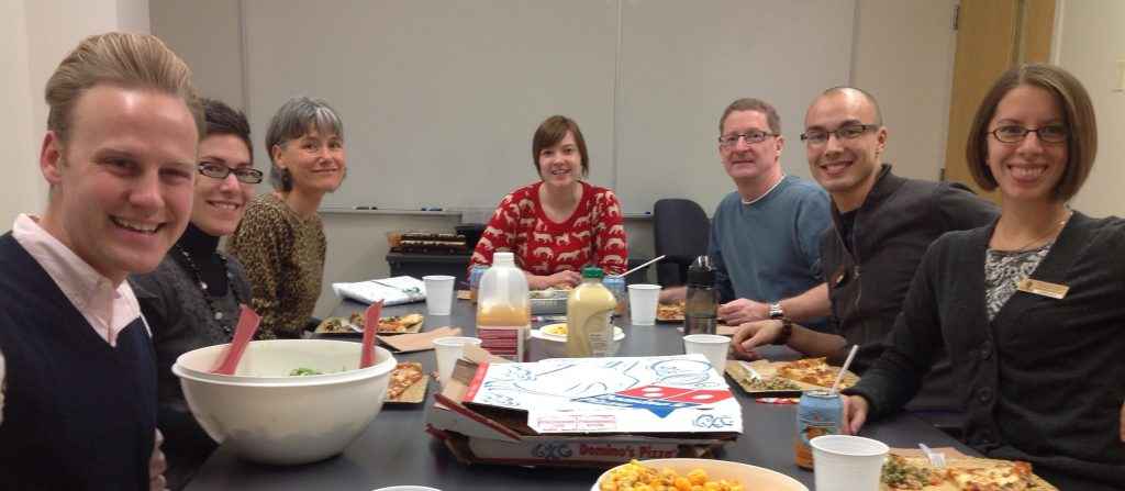 Seven library staff members around a rectangular table with pizza, salad and drinks on it