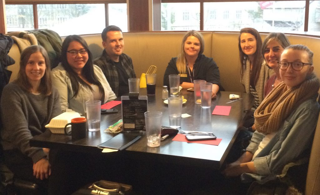 Seven library staff members around a restaurant table